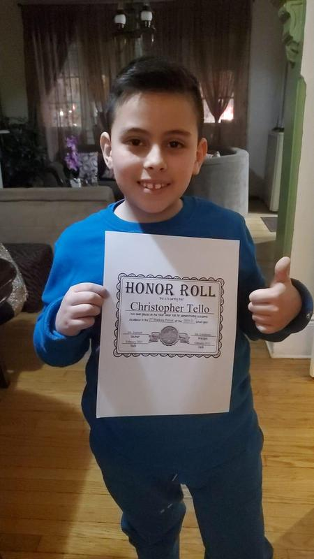 Christopher holding honor roll certificate