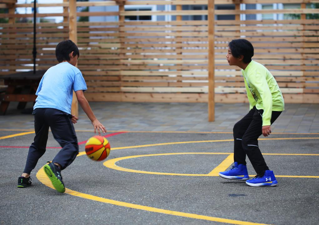 Two boys with short, black hair and dark skin play basketball.