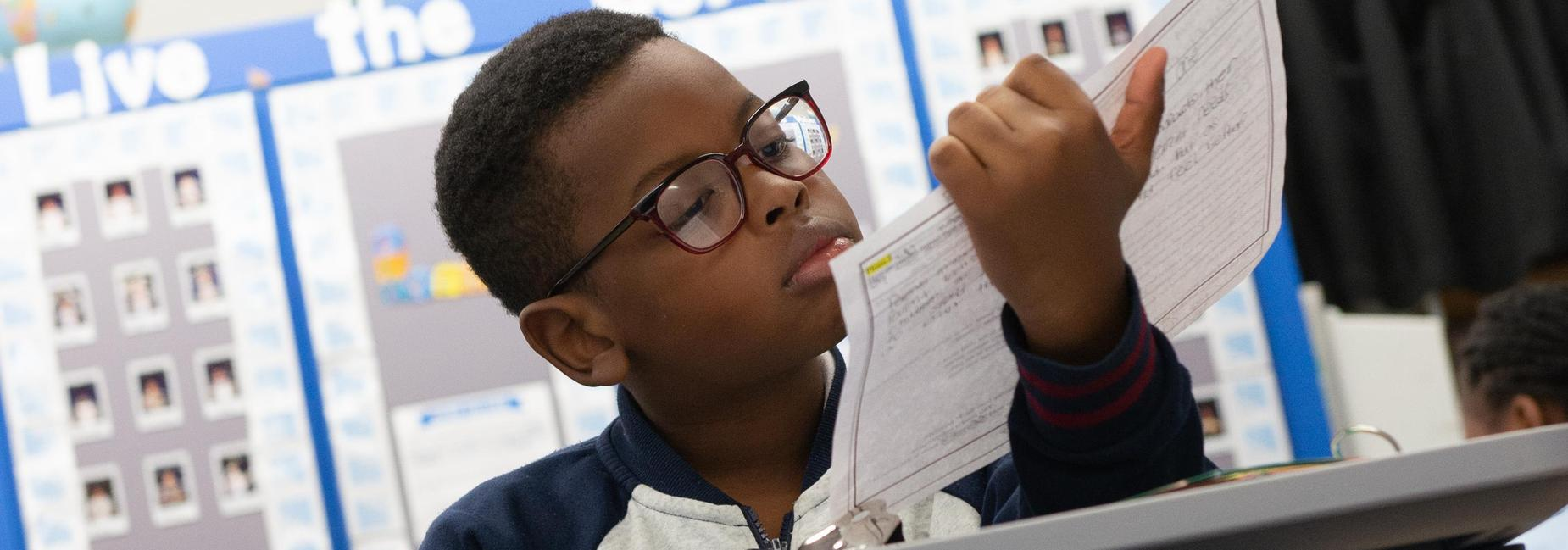 An elementary school student reading over a sheet of paper.