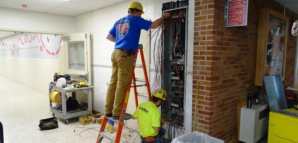 This snapshot features two members of Weydman Electric's electrical construction crew re-wiring a segment of the main campus electrical power wiring system.