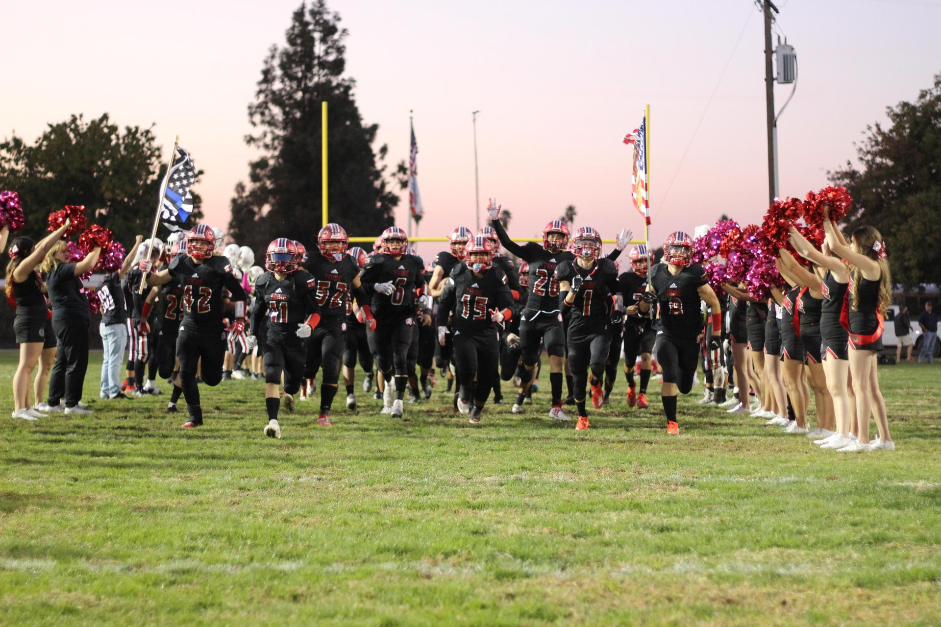Tribe Varsity Football Players Running on to the Field