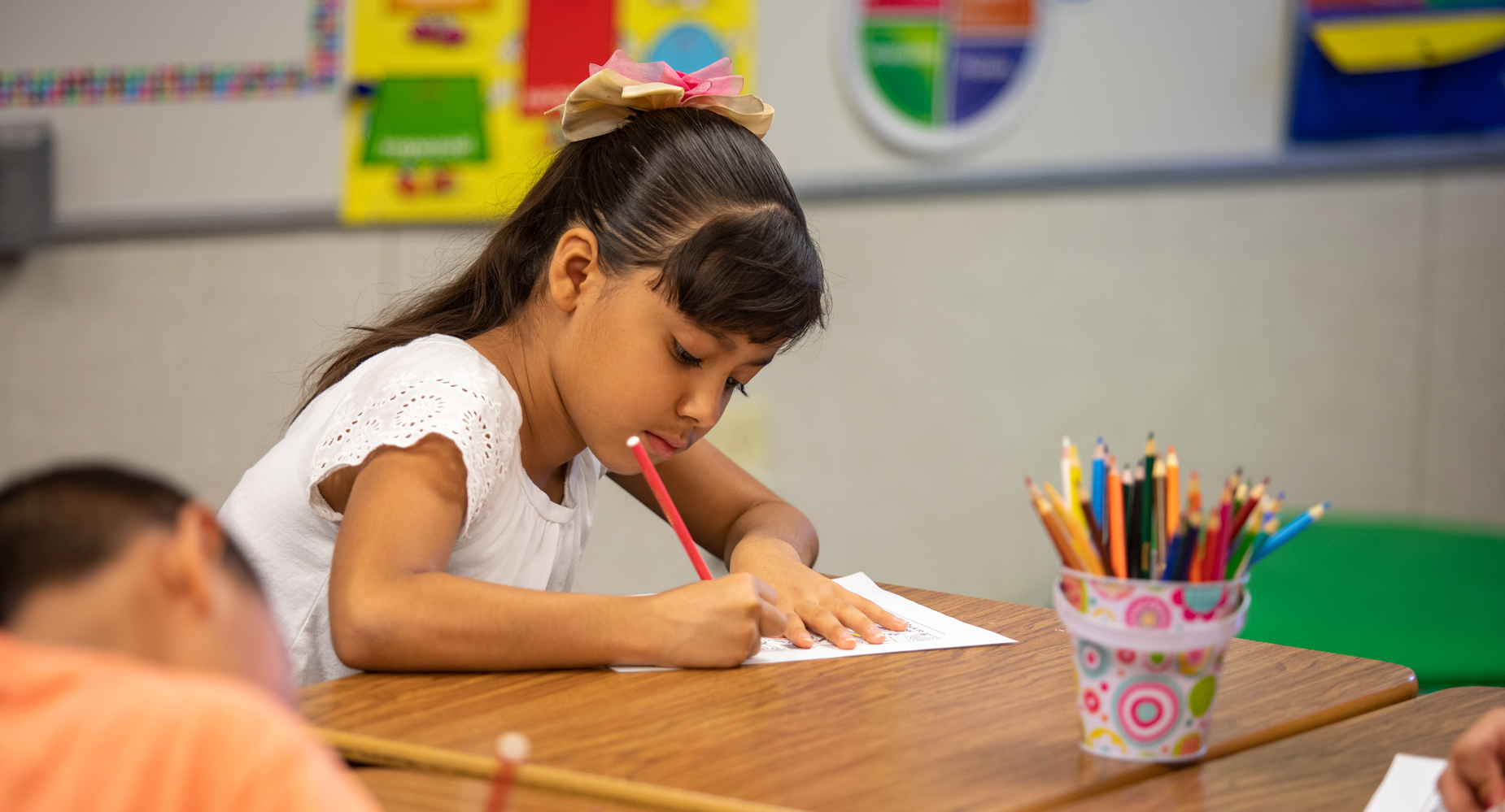 Girl at school desk coloring