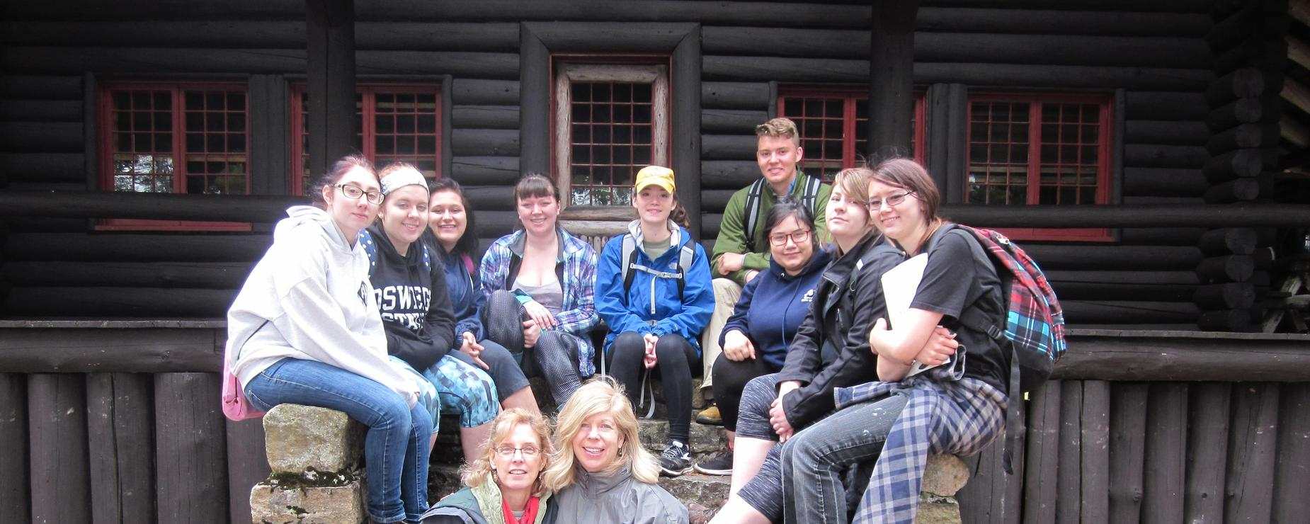 Environmental club poses for a picture outside of a log cabin