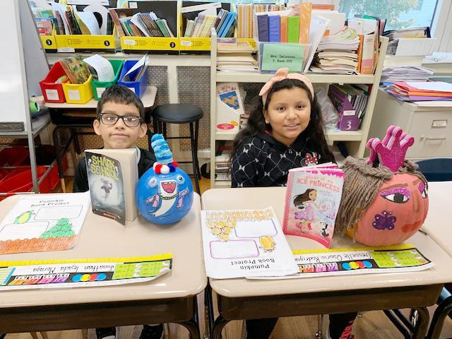 Two students display their book-report project, which incorporated the decorating of a pumpkin