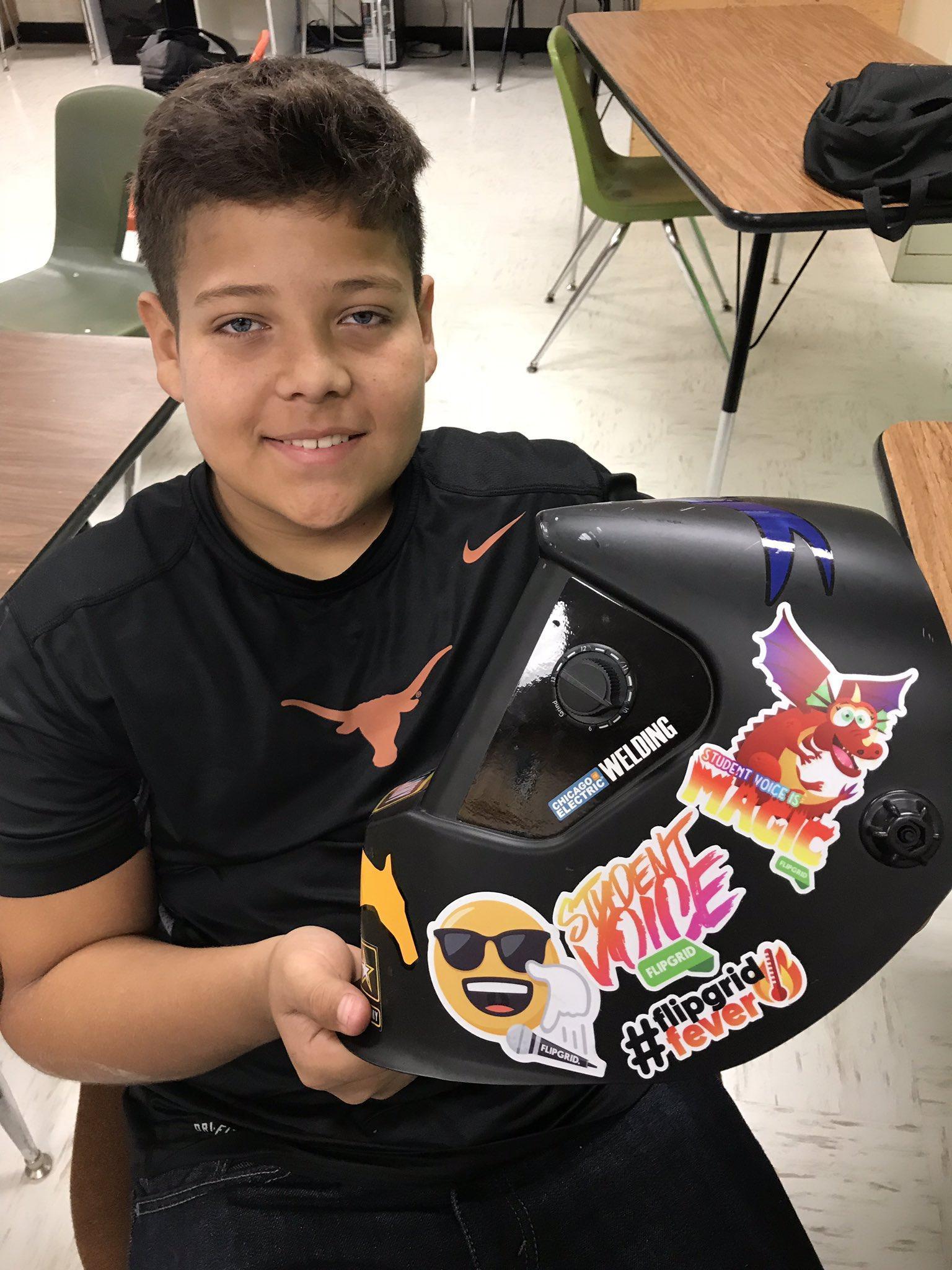student smiling holding welding helmet