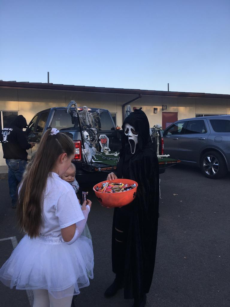Girl looking at bucket of candy held by person with a mask