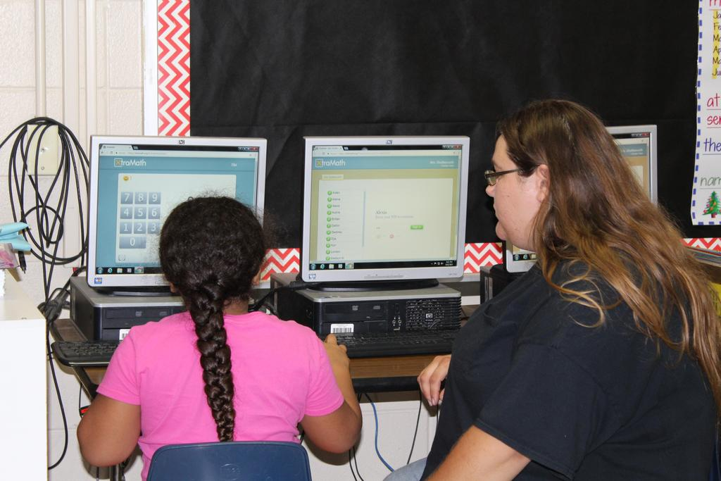 student showing computer program to parent