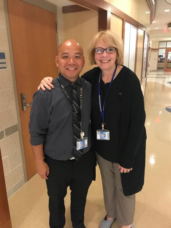 two support teacher happily welcoming parents