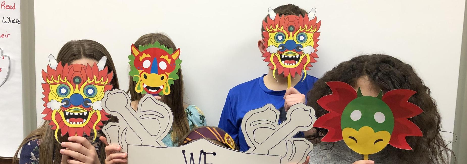 Students holding dragon masks in front of face