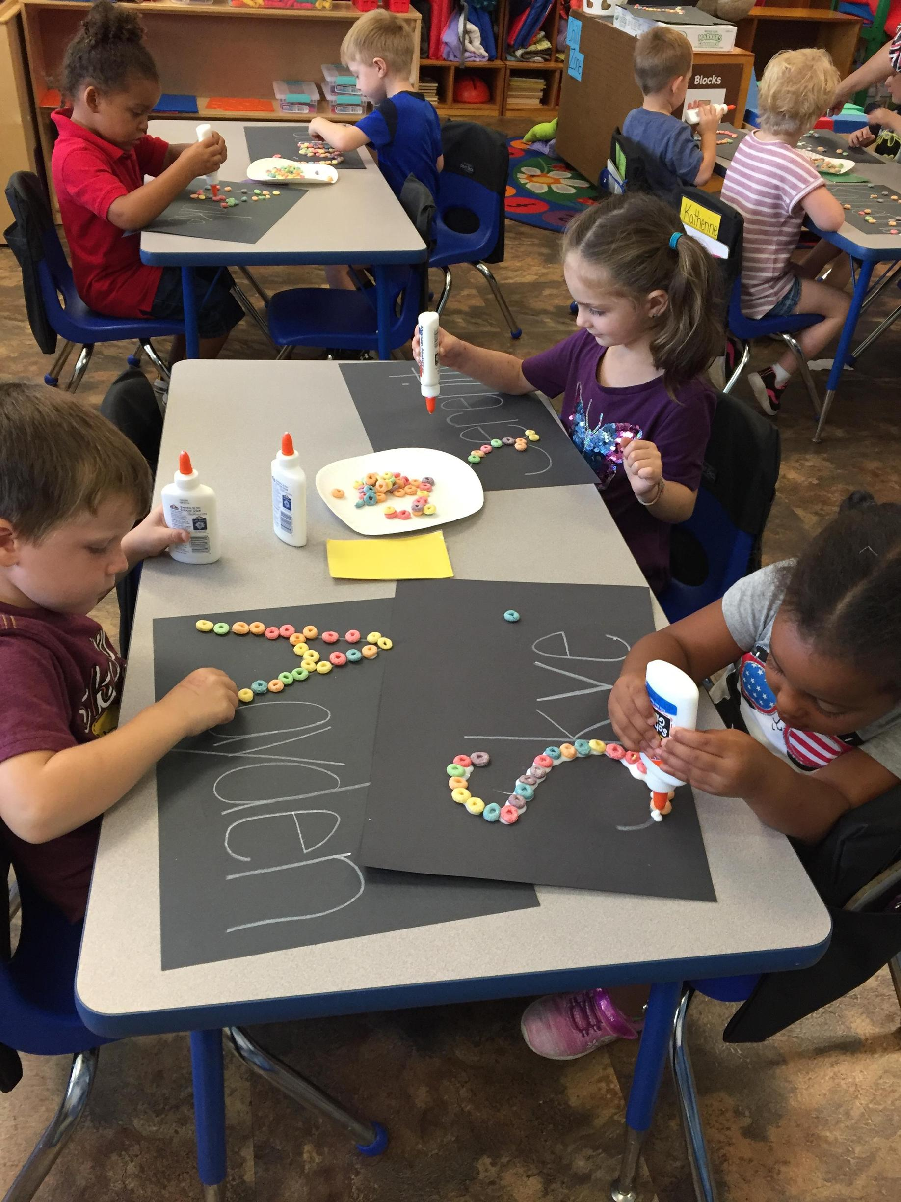 Pre-K works with fruit loops to write their name.