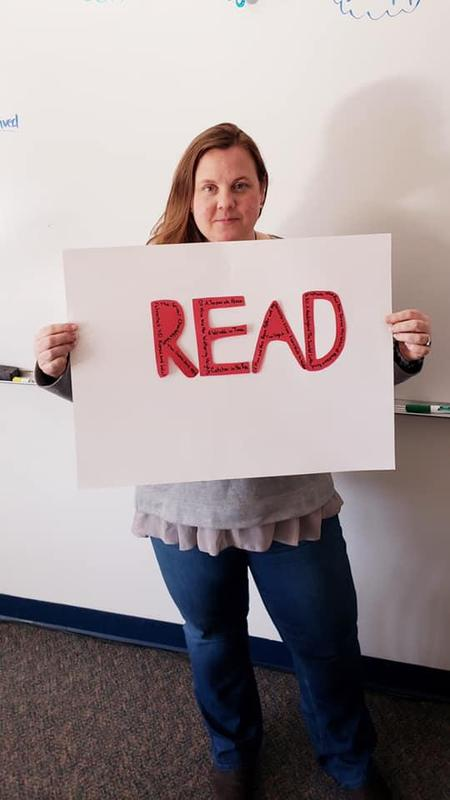 teacher holding sign saying