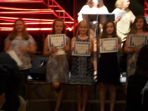 Students hold certificates.