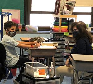 Photo of Wilson student and teacher wearing masks during instruction.