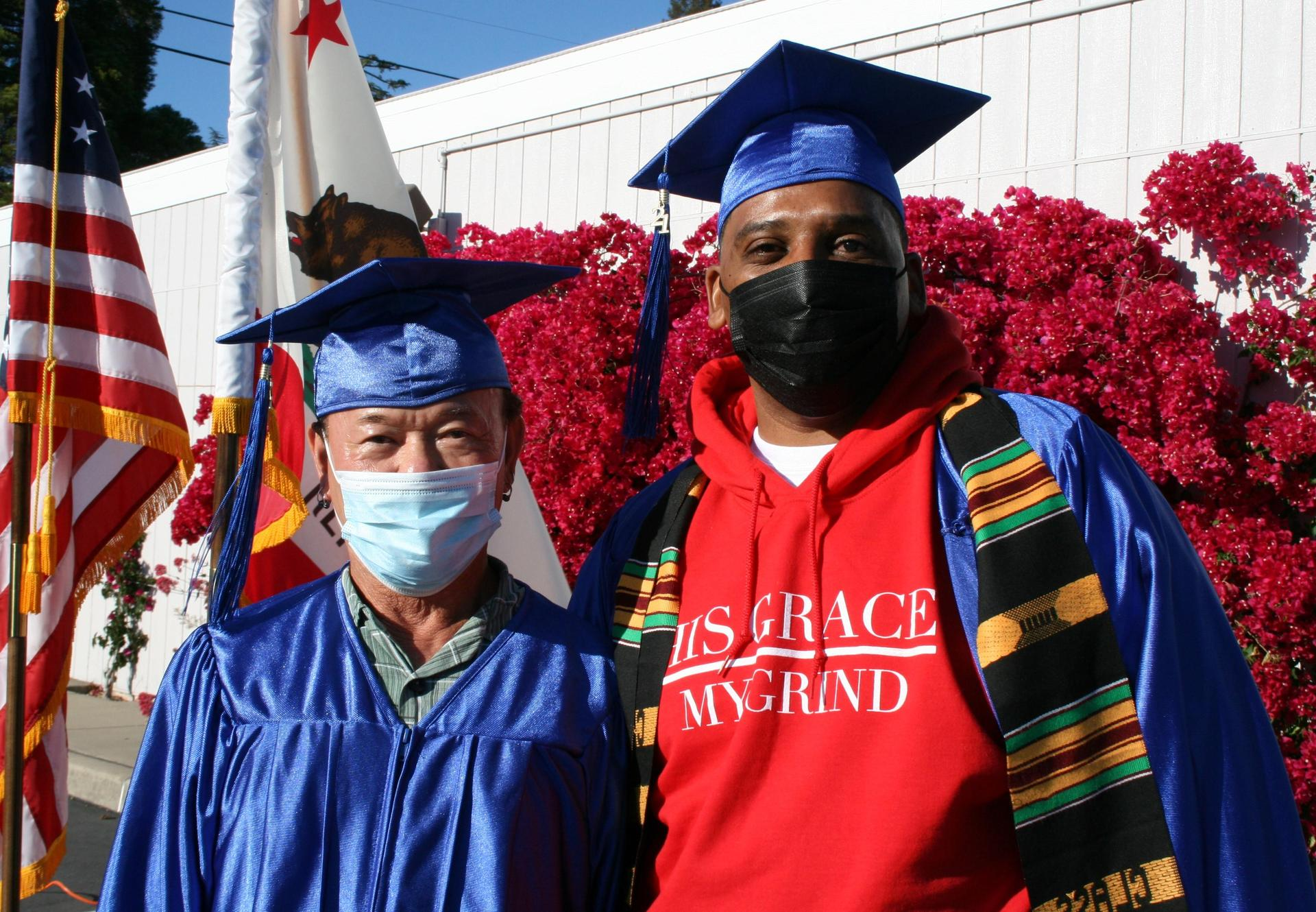 Two graduates from 2021 in cap and gown, smiling.