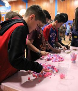 Photo of Tamaques 5th graders as they try to pick up a small fuzzy ball with chopsticks during a Valentine's Day activity.