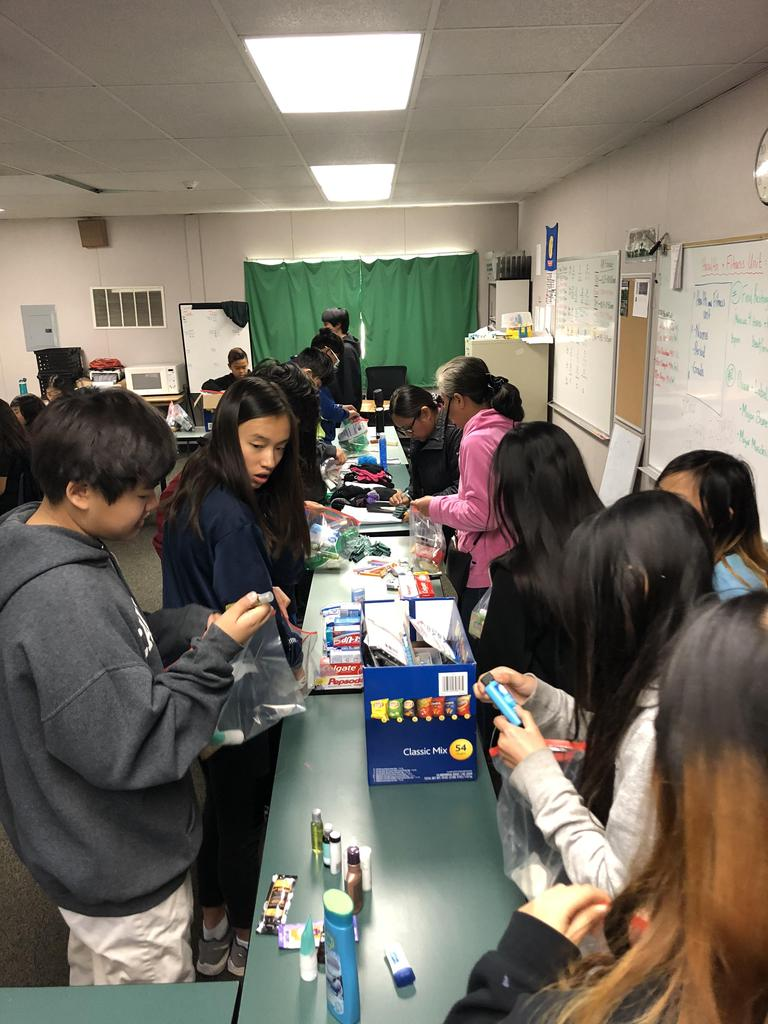 A group of people working in an assembly line to create care packages.