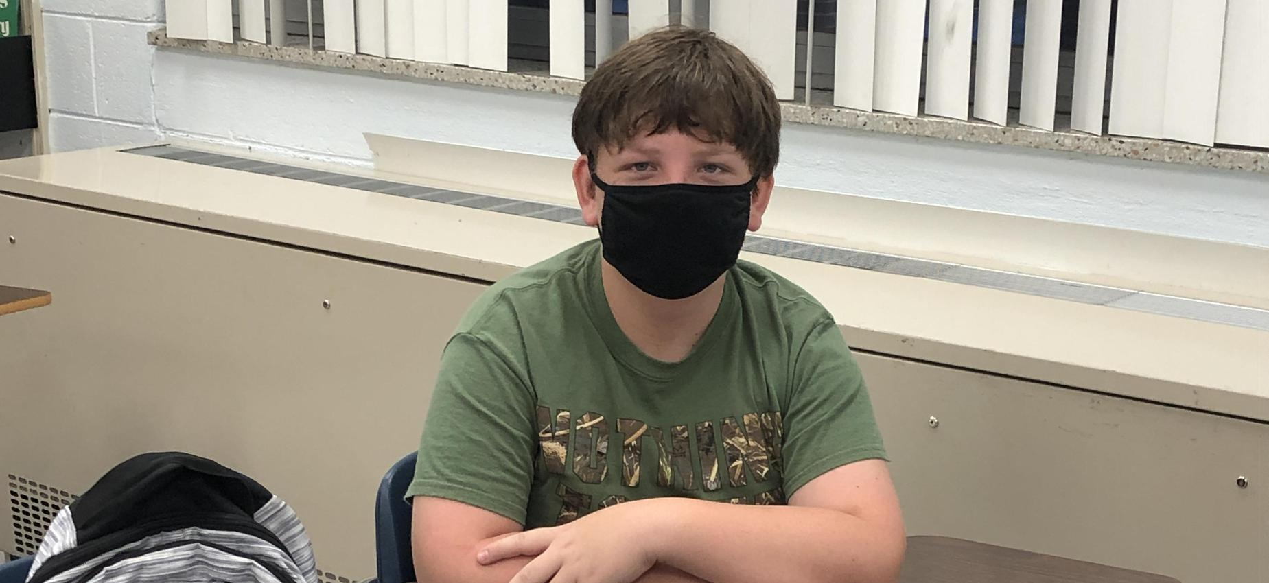 A student wears a mask while sitting at a desk.