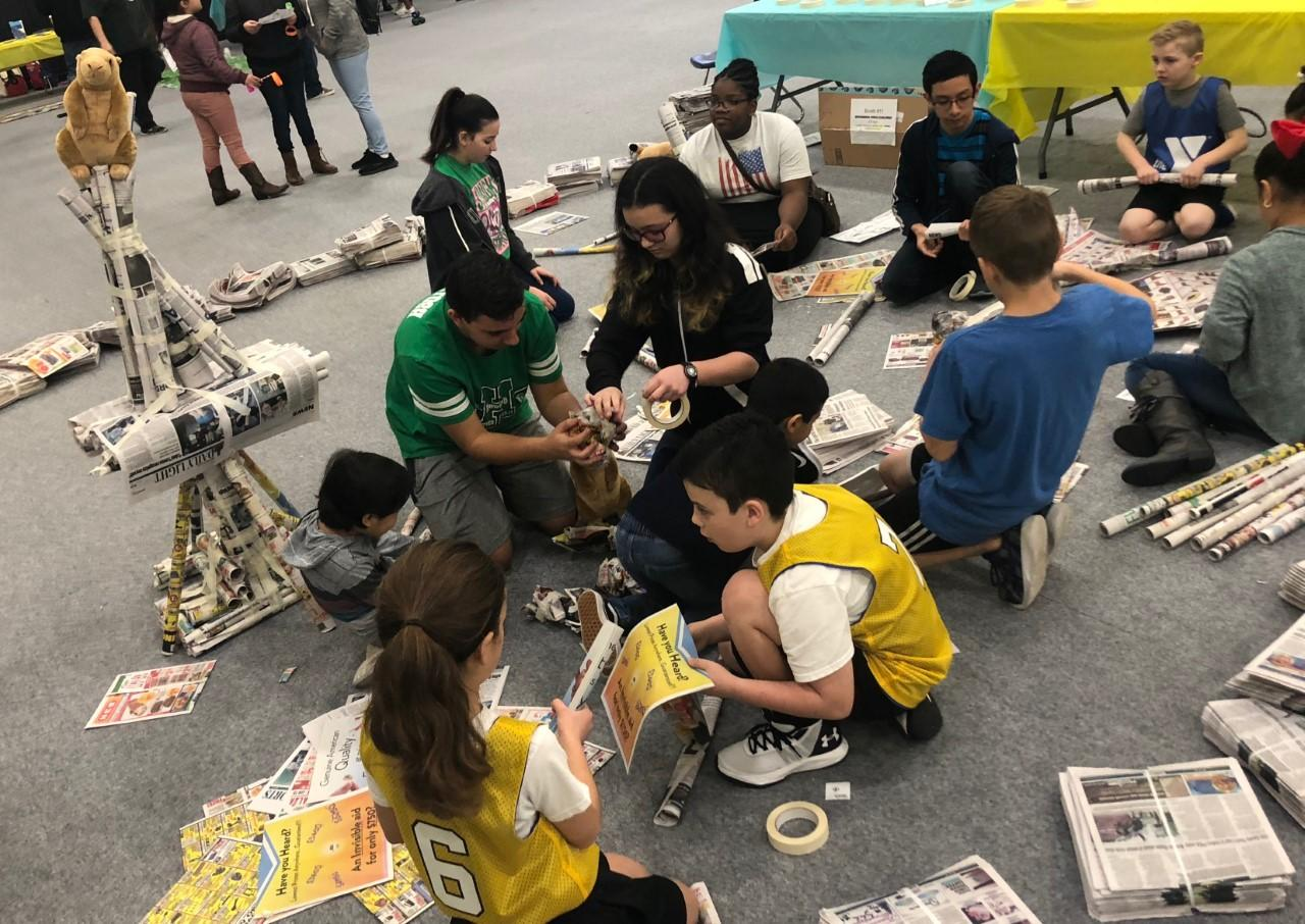 group of students building objects with newspapers
