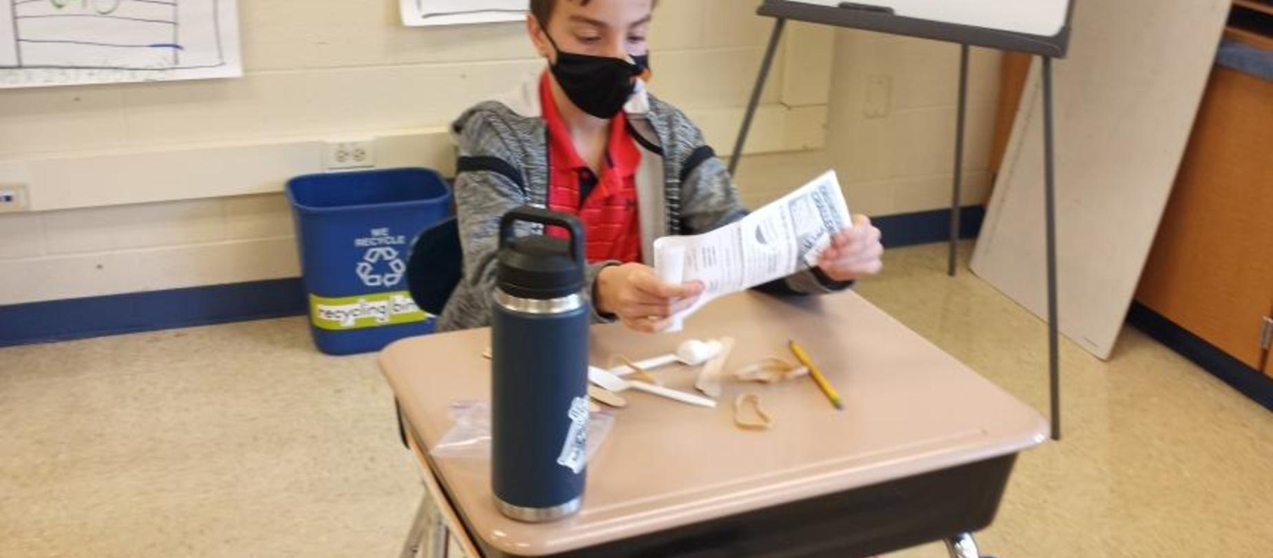 boy wearing a mask working on a project