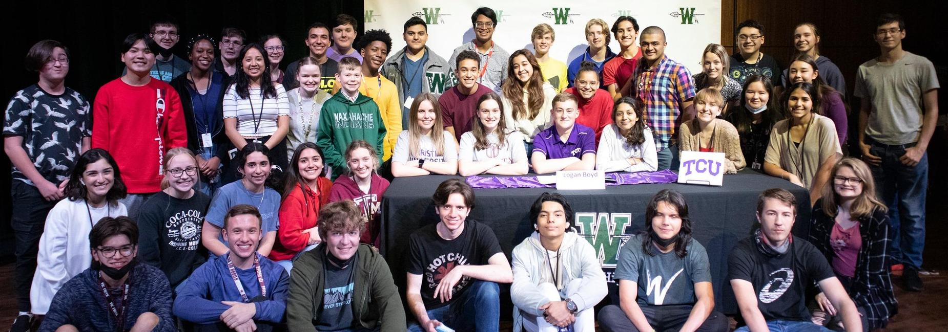 large group of teens on the stage at the athletics and fine arts signing day ceremony