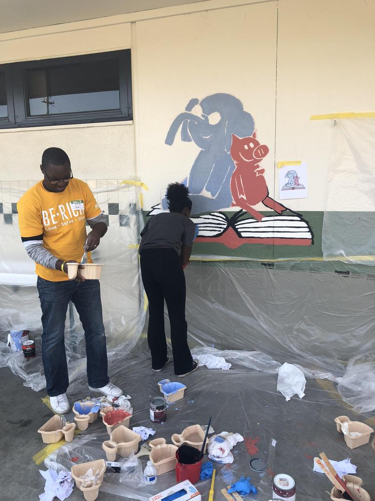 two NBCC members paint mural on wall