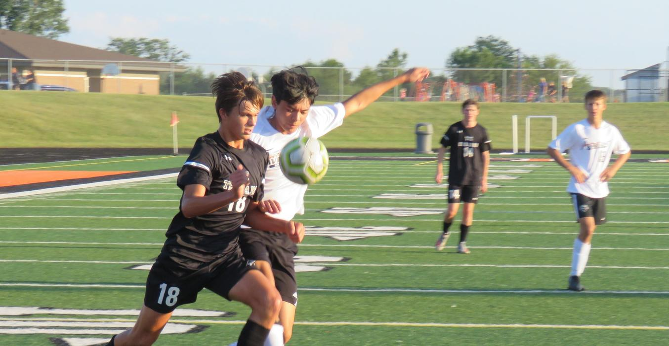 A varsity TK soccer player races to the ball.