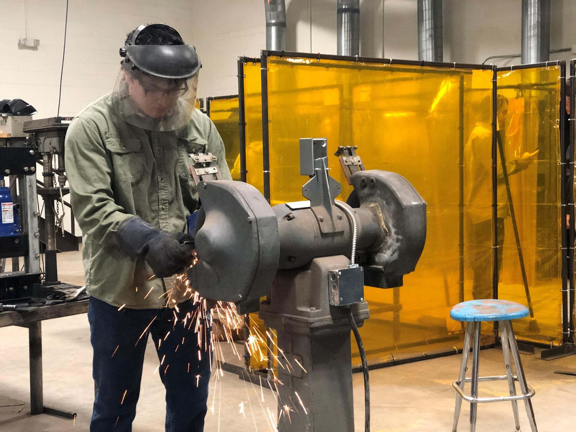 welding student at machine in classroom