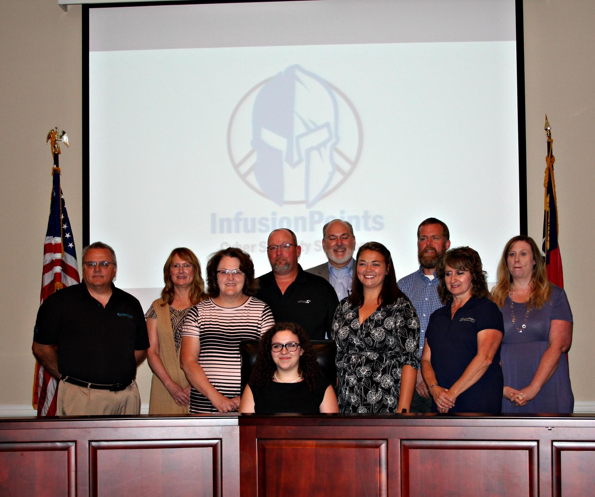 Hannah Billings poses with her family in the Board Room during apprenticeship signing.