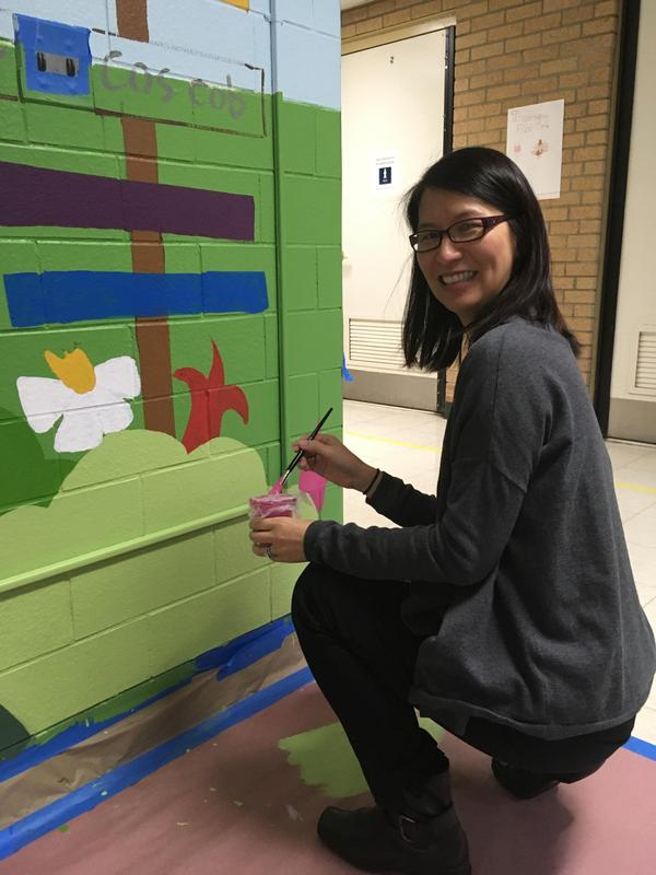 Jefferson School principal Dr. Susie Hung lends an artistic hand as students and parent volunteers join together to paint several murals in school hallways.