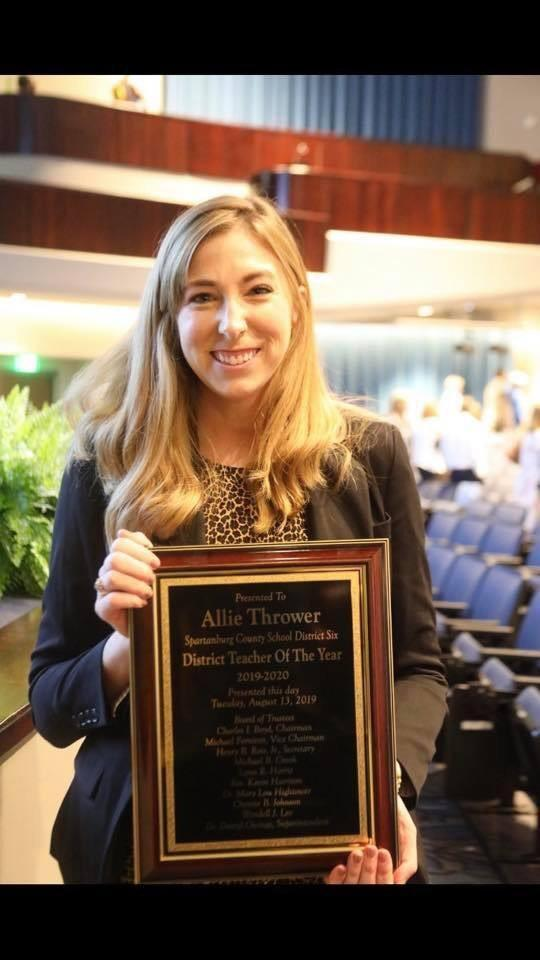 Allie Thrower holds a plaque saying teacher of the year.