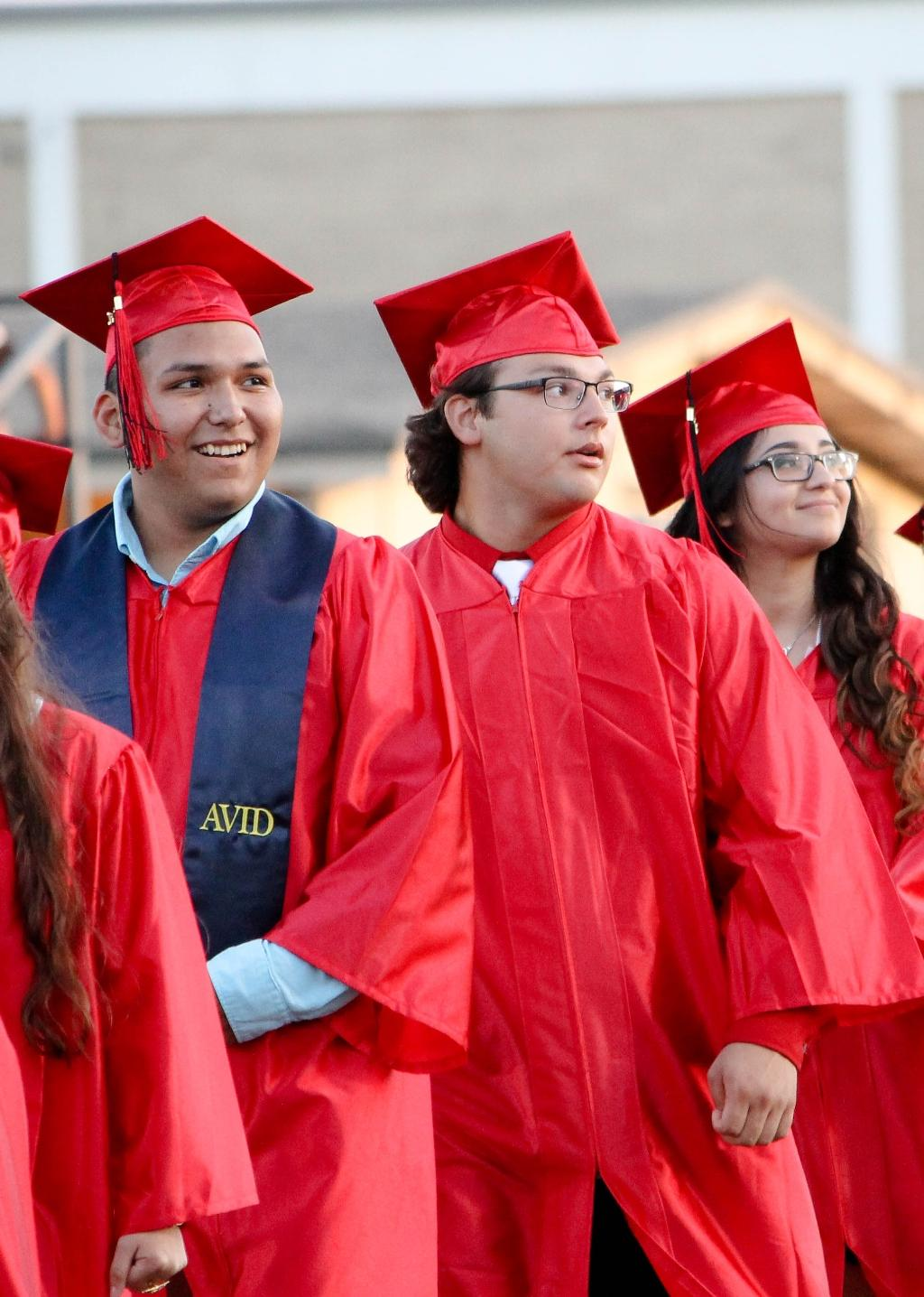 two male and one female student walking toward the memorial stadium field, smiling at the crowd in the stands, for the 2018 victoria east high school graduation