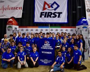 Bensalem High School Robotics Team dressed in royal blue shirts holding a banner naming them Champions