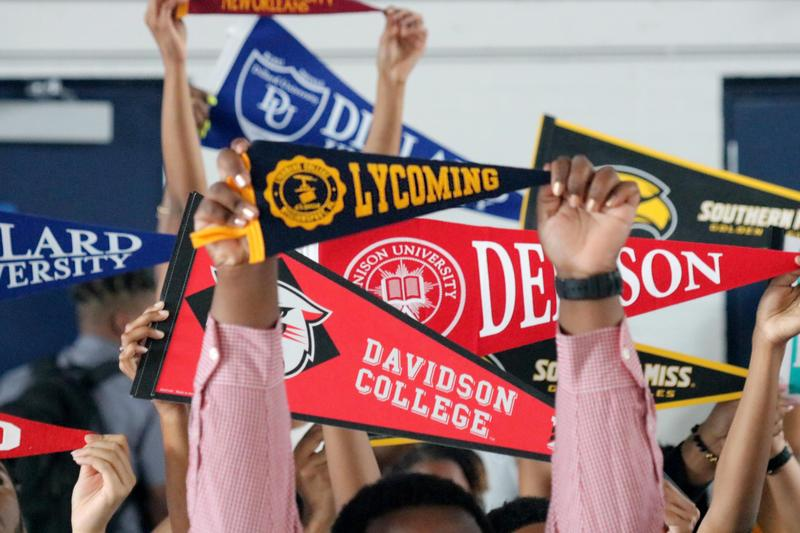 Alumni holding up their college pennants