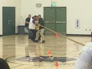 a group of teachers pulling one side of a tug-of-war rope with an orange flag tied to the middle of the rope