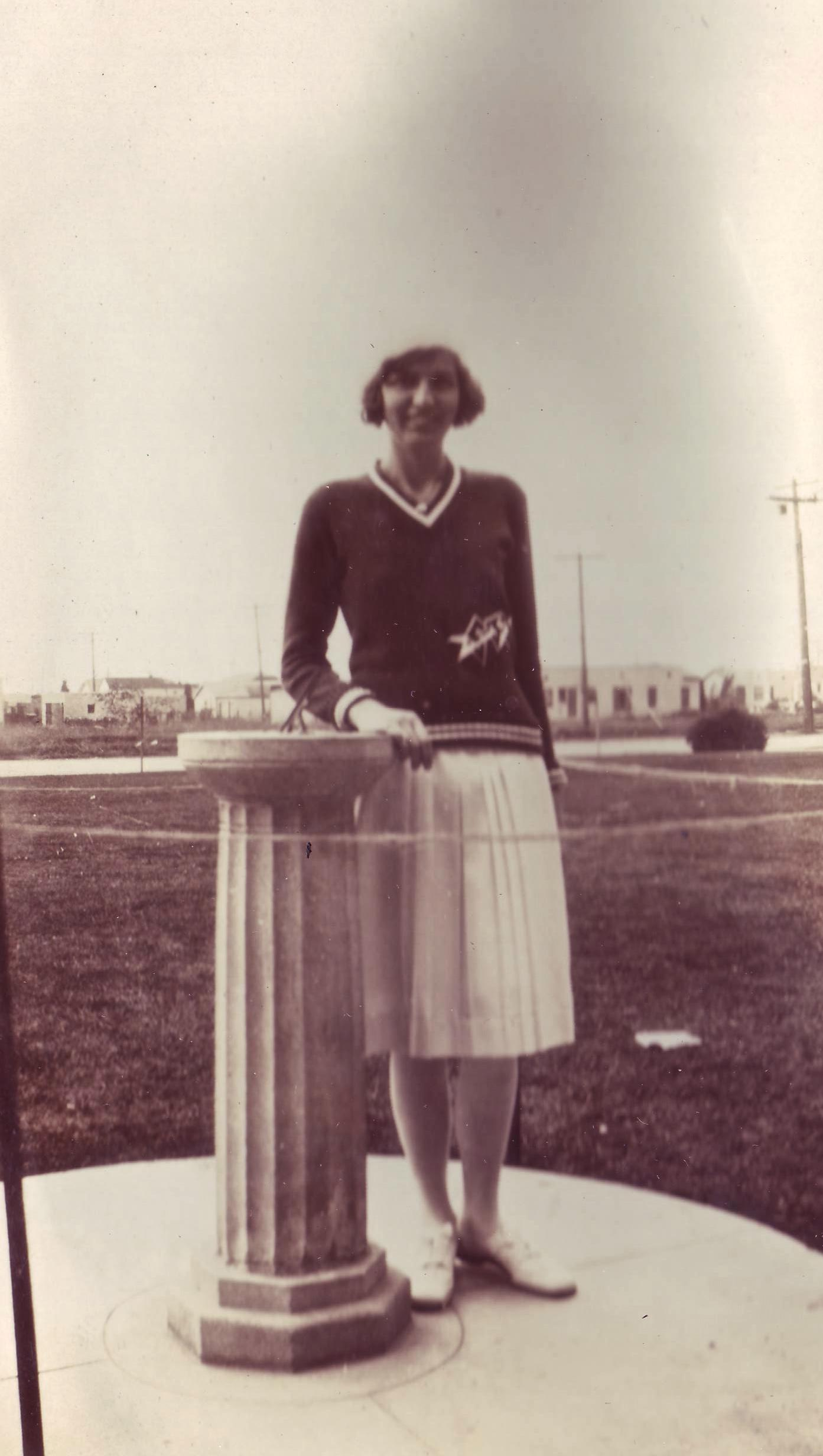 Margaret Griffith posing with the 1930 Class gift, a sundial that welcomed everyone to Garfield
