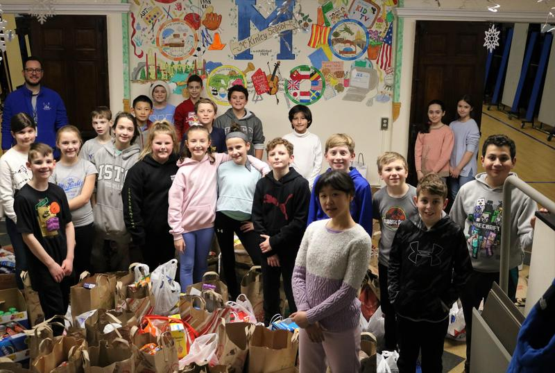 Photo of McKinley principal Dr. Marc Biunno with group of students and lots of bags of non-perishable items collected during annual