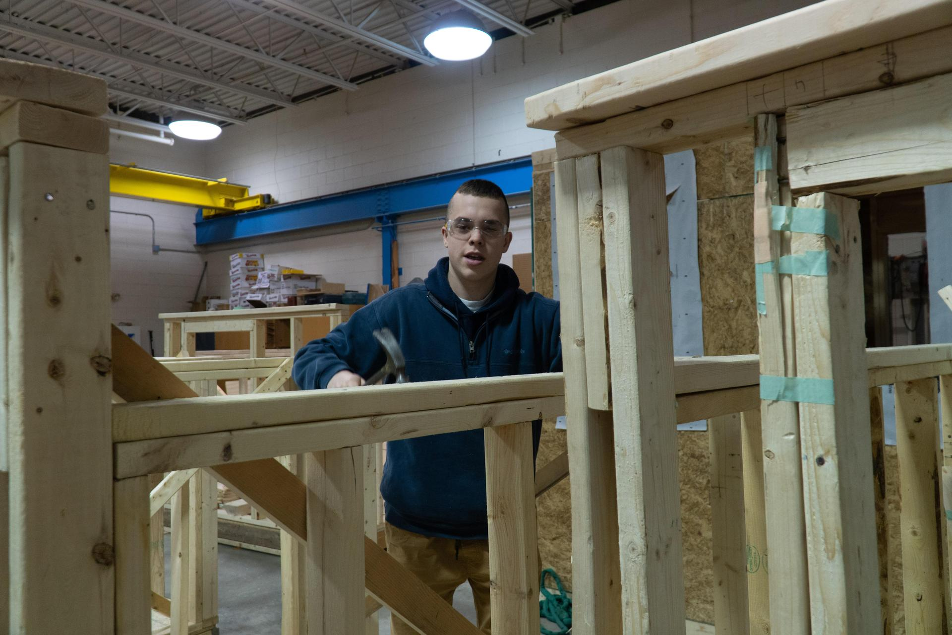 Student with wooden shed frame
