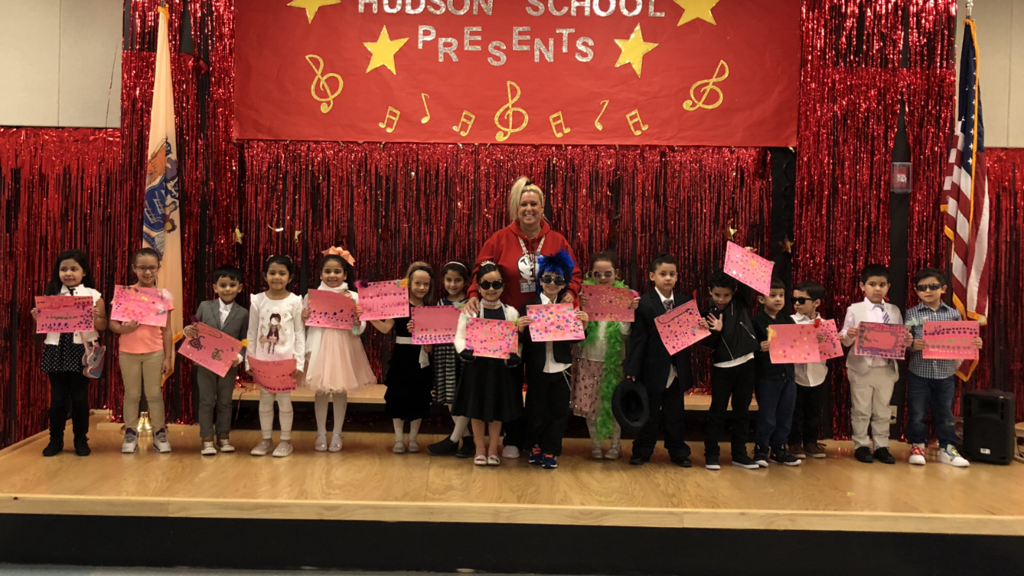 Kindergartners dressed as their favorite book characters on stage with their teacher