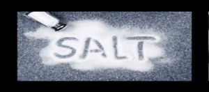 salt shaker spilling salt, the word salt spelled out in the spilled salt