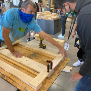 teen and instructor work on building wooden bunk bed
