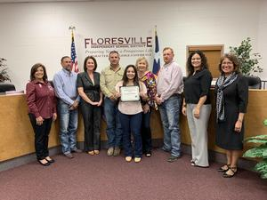 Yesenia Arellano displaying the Community of Character Award with the Board of Trustees