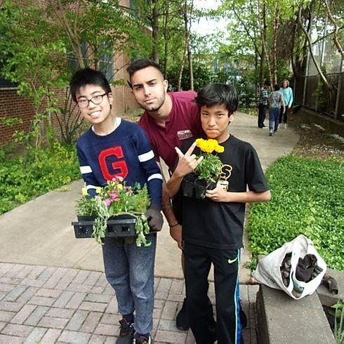 students holding plants with camp counselor