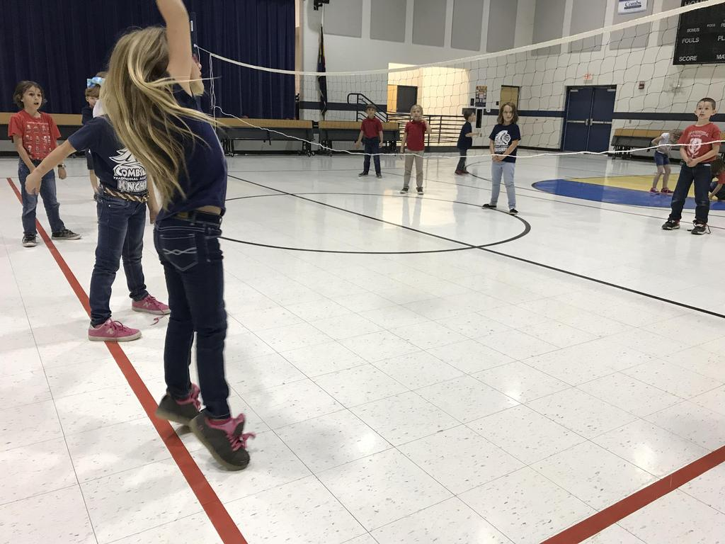 Having fun playing volleyball in PE