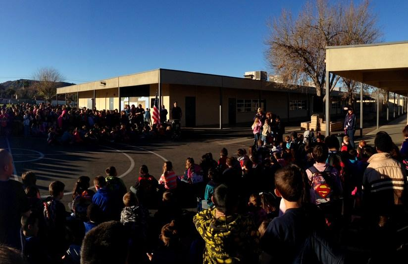 a different view of students listening to the principal during an outside school assembly
