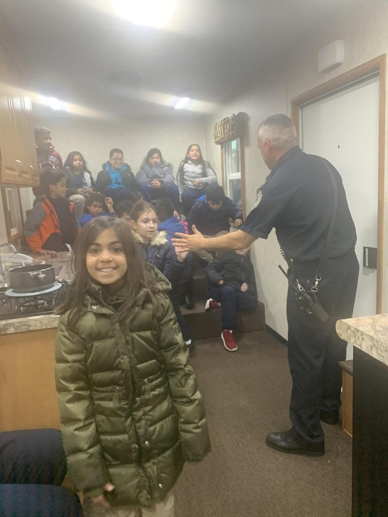 close up of a girl standing by the stove while the fireman explains safety to the children seated on the steps of the fire safety house