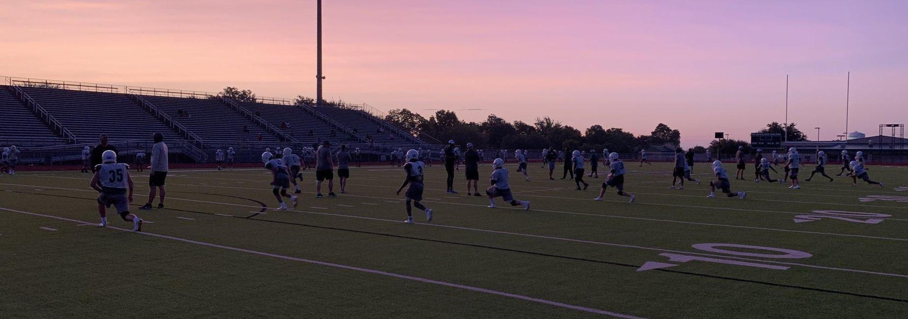 football players in uniform on the field at sunrise