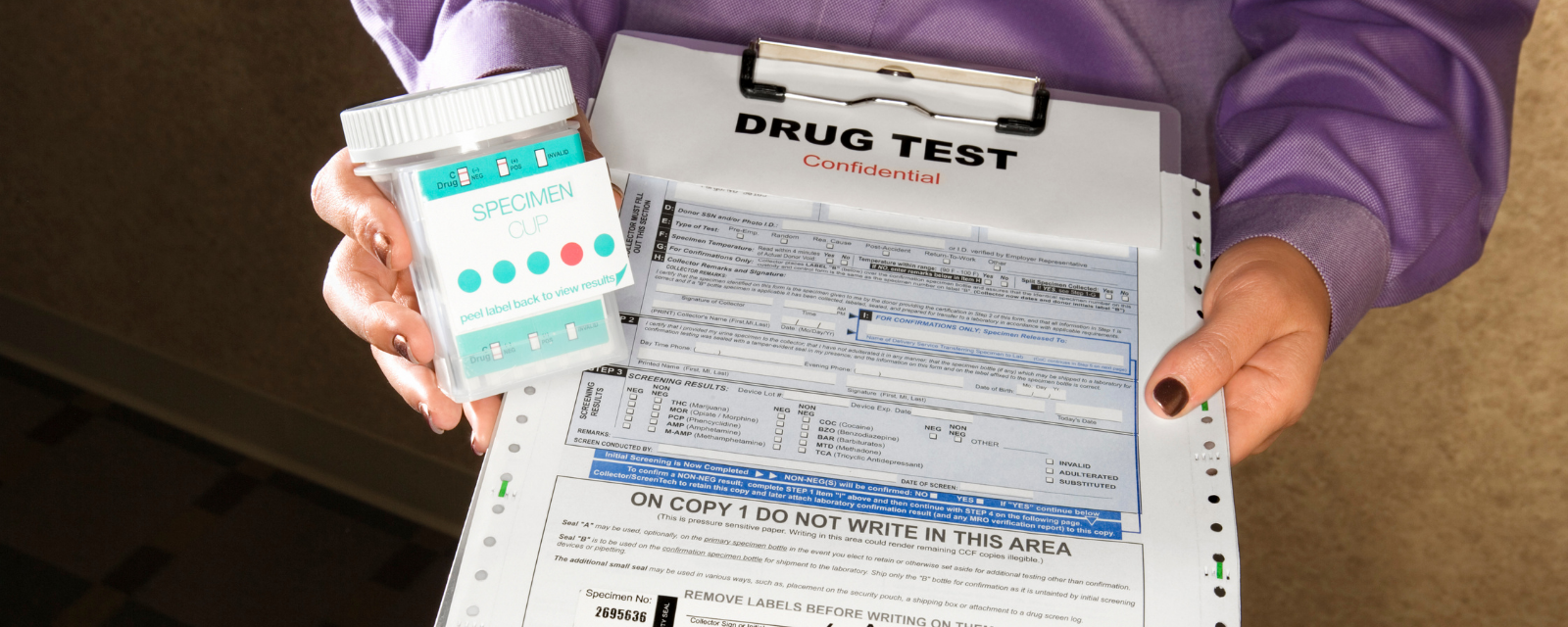 woman holding clipboard with drug test form and cup labeled specimen cup