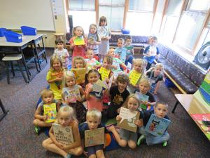 Cathy Leaf's kindergarten class shows the books they received from community sponsors.