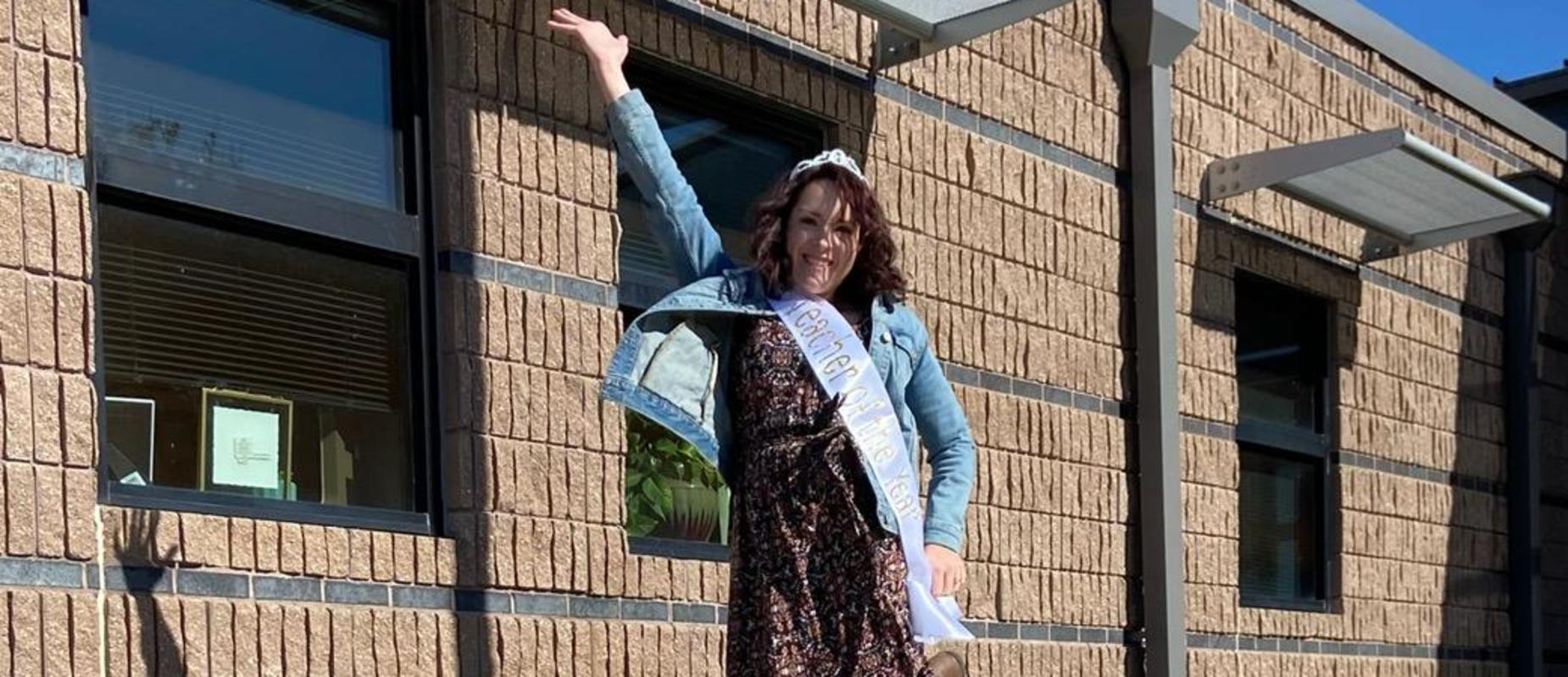 Teacher jumping in the air with a crown on