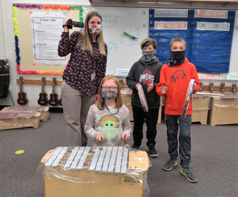 Lee and Page Elementary music teacher Jennifer Filipiak is pictured with three students showing the new items they were able to purchase with the three grants.